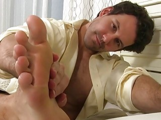 Tired businessman plays with his toes to relax
