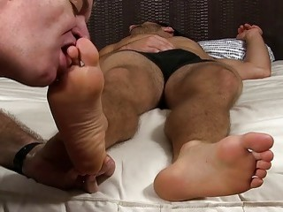Sleepy hunk has his bare feet licked and toes sucked