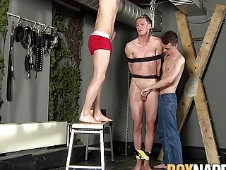 Submissive dude tied to the ceiling and fucked by two twinks
